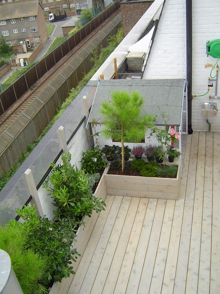 View of kid's playhouse and shrubs on roof terrace garden in Mile End